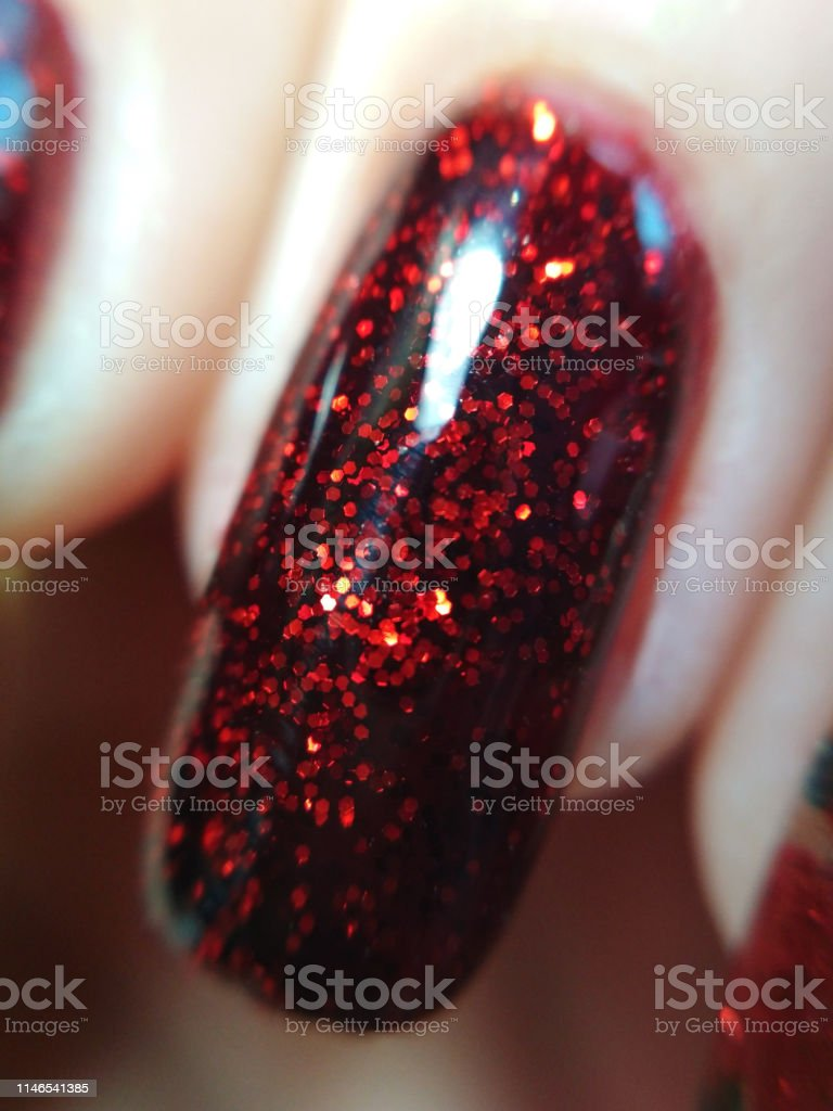 Woman hand finger black and red manicure gel nail polish swatch...