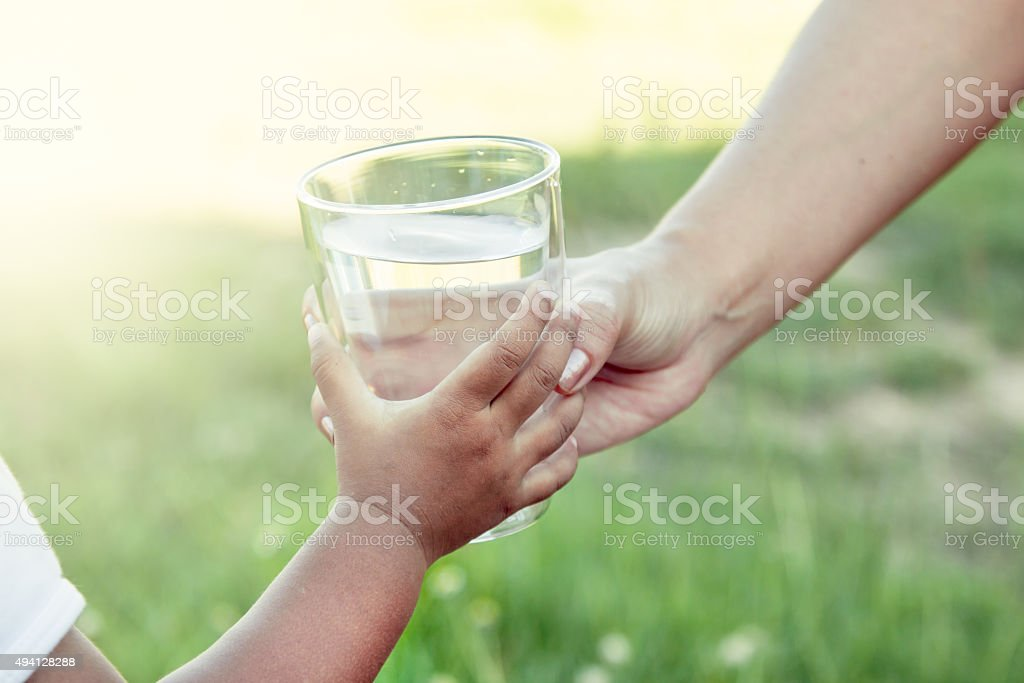 Woman hand giving glass of fresh water to child