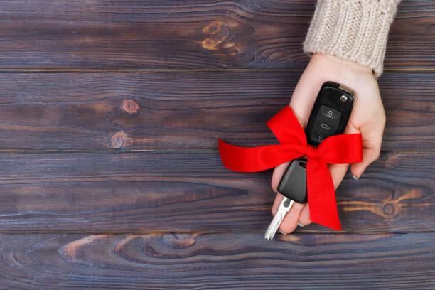 frau hand halten fahrzeugschlüssel mit roter schleife. ein auto verschenken - autoschleifen stock-fotos und bilder