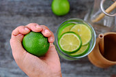 istock woman hand hold lemons and lime slices for detox water 1170678879
