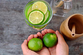 istock woman hand hold lemons and lime slices for detox water 1170679210