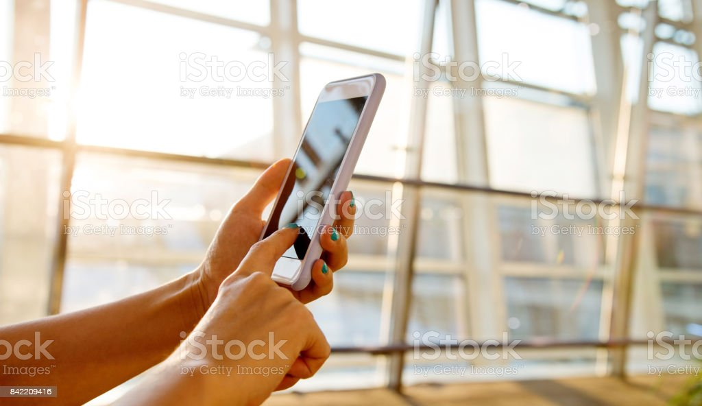 Woman hand hold smart phone at airport stock photo