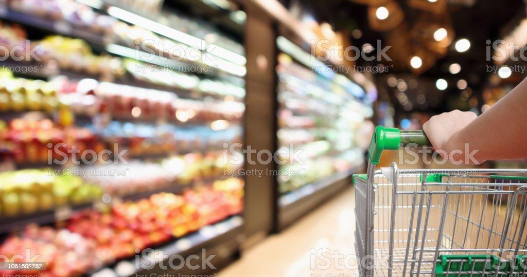 asimiento de la mano de la mujer supermercado carrito borroso abstracto orgánico frutas frescas y vegetales en los estantes de supermercado defocused bokeh fondo claro - Foto de stock de Adulto libre de derechos