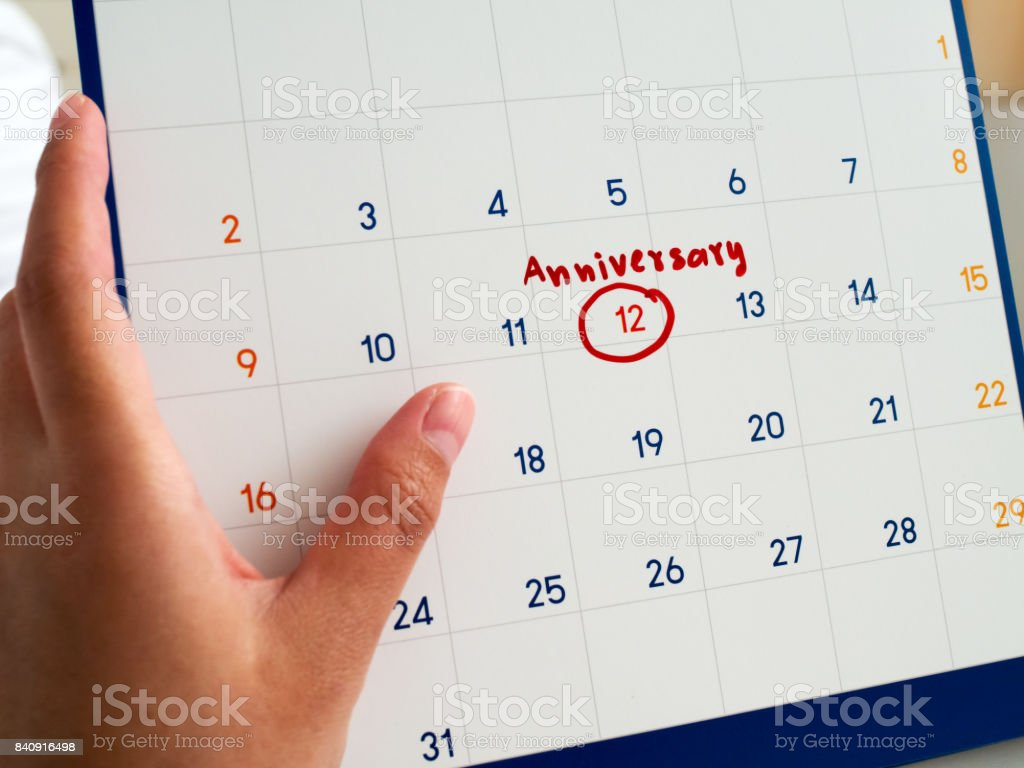 女性手は、赤い丸を書かれた白いカレンダーと白のカレンダーにマーク周年単語を保持します。この記念日は大事な約束を思い出させるマーカー。 ストックフォト