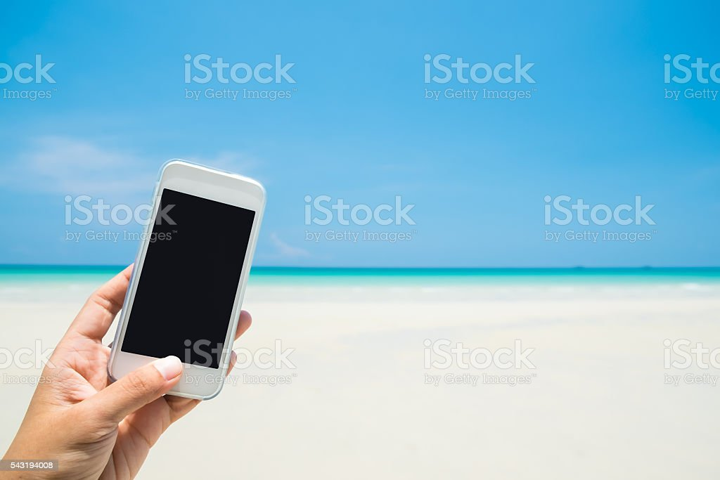 Woman hand hold white mobile phone with sea beach stock photo