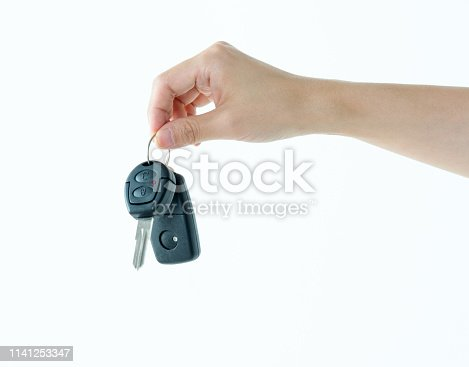 539841066 istock photo Woman hand holding a car key 1141253347