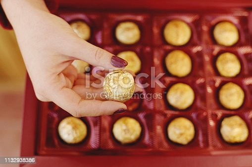 Woman hand holding a chocolate piece  in box for valentine's day