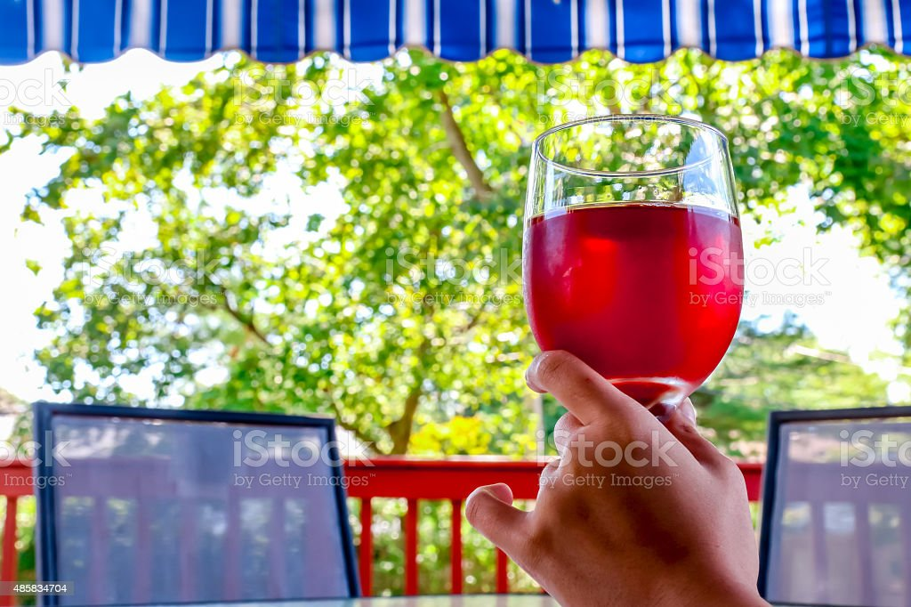 woman hand holding a glass of red wine stock photo