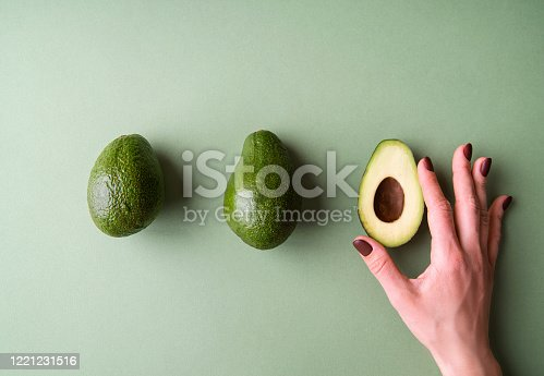 Healthy food concept. Woman hand holding a half of avocado on the green background top view