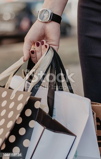 istock Woman hand holding a lot of purchases 1038158134