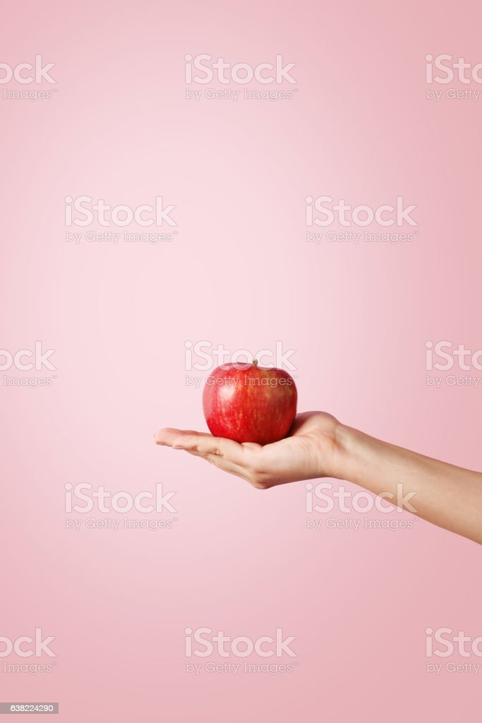 Woman hand holding a red apple on pastel background stock photo
