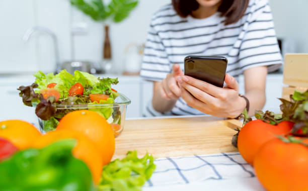 Woman hand holding a smartphone and salad bowl with tomato and various green leafy vegetables on the table at the home, take your advertising. stock photo