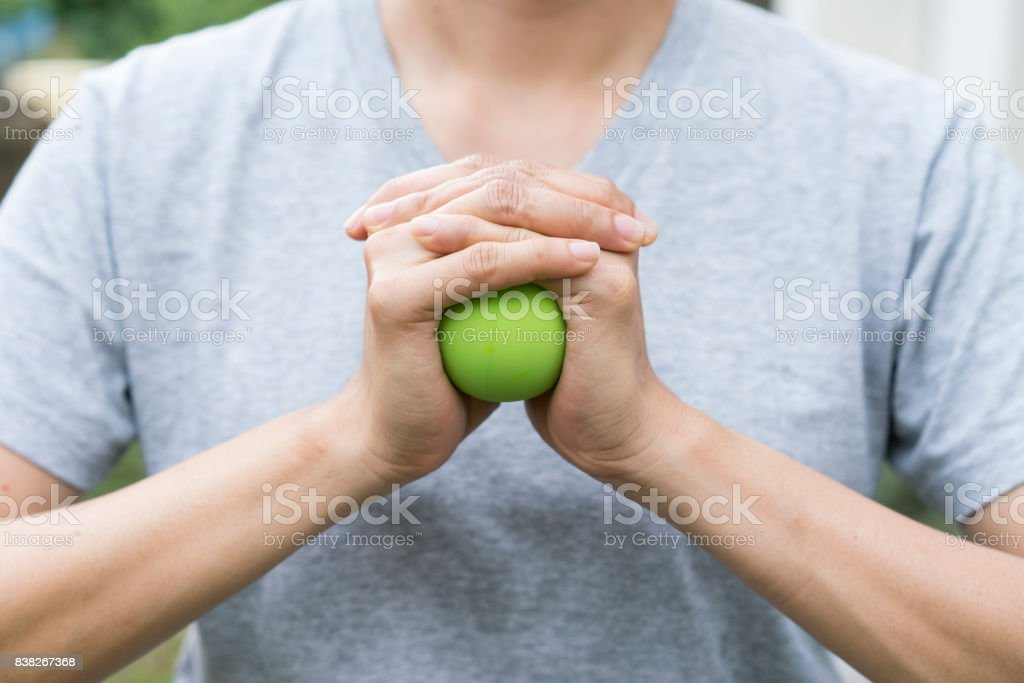 woman hand holding a stress ball stock photo