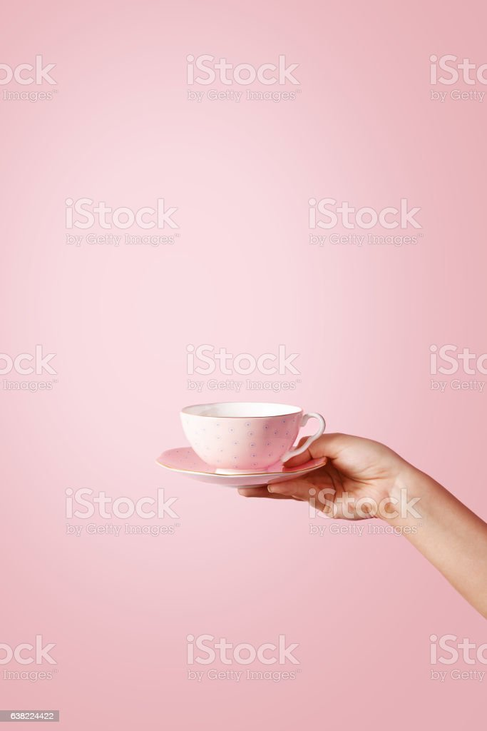 Woman hand holding a teacup on pastel background stock photo
