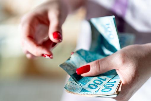 Vrouw Hand Bedrijf Een De Munteenheid Van Reais Braziliaanse Geld Stockfoto en meer beelden van Bankieren