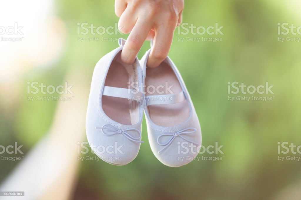 Woman hand holding baby shoes stock photo
