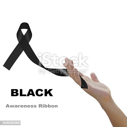 istock Woman hand holding black  ribbon  against white background for Melanoma and mourning concept 846068388