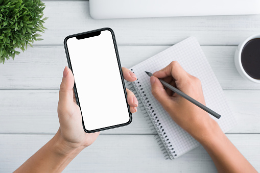 1084491176 istock photo Woman hand holding blank smartphone and writing in notebook 1086864088