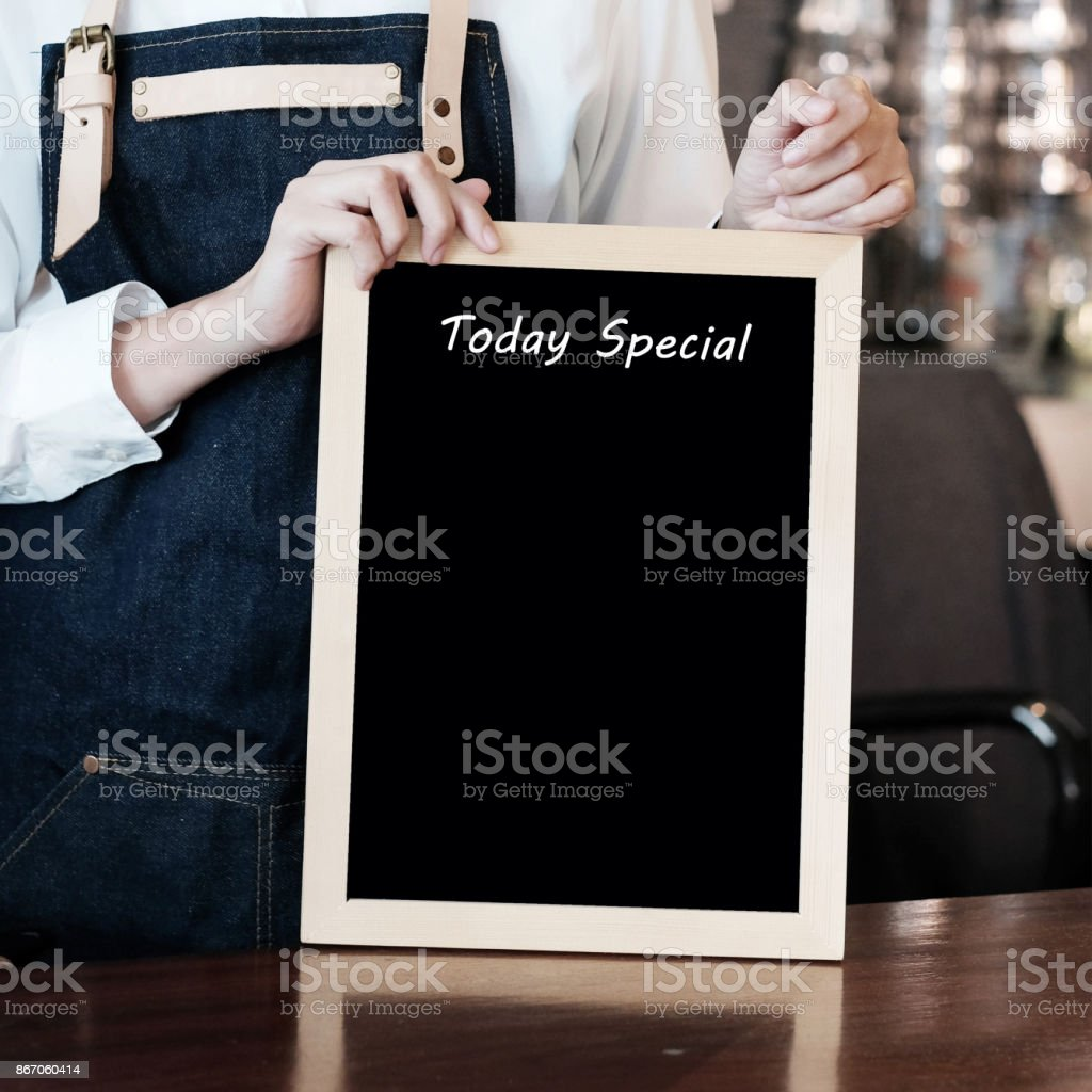 Woman hand holding blank Today special board over blur cafe background, copy space for text, food and drinks background stock photo