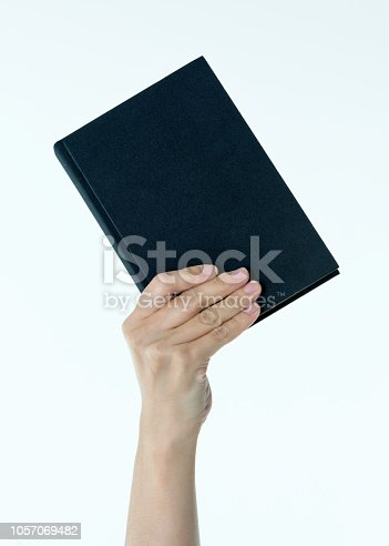 Woman hand holding book on white background.