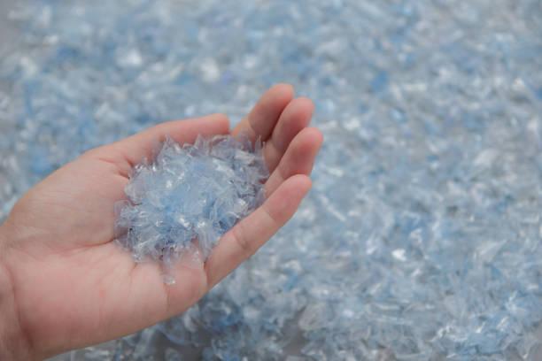 kvinnan handen håller flaskan flake, pet flaska flake, plastflaska krossade, små bitar av cut blå plastflaskor - pet bottles bildbanksfoton och bilder