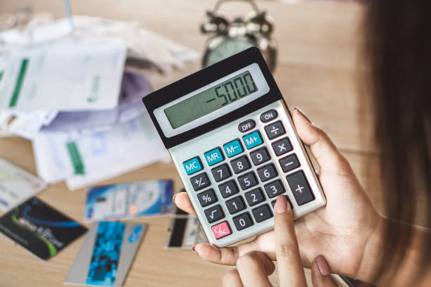woman hand holding calculator showing number budget deficit for credit card debt woman hand holding calculator showing number budget deficit for credit card debt payment with some bills on desk minus sign stock pictures, royalty-free photos & images