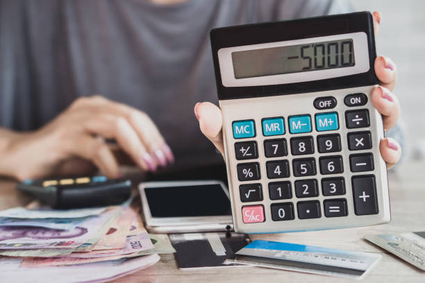 woman hand holding calculator with budget deficit for credit card debt woman hand holding calculator with budget deficit for credit card debt payment with some banknotes and phone on desk minus sign stock pictures, royalty-free photos & images
