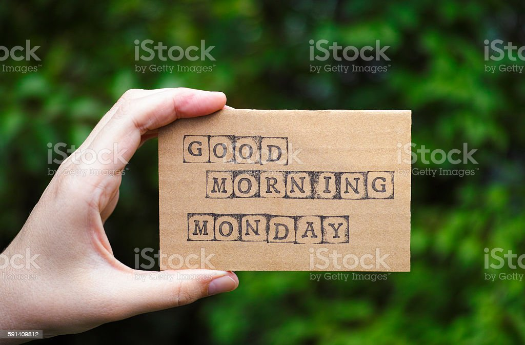 Woman hand holding card with words Good Morning Monday stock photo