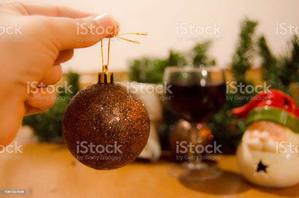 woman hand holding christmas ball and wine glass with christmas ornaments in the bacground stock photo