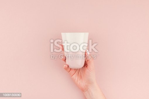 istock Woman hand holding coffee cup on pink background 1009130030