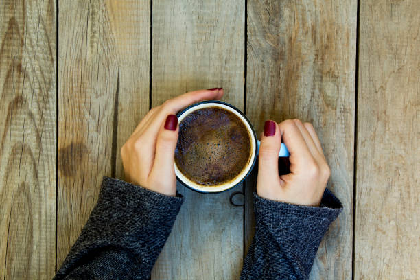 frau hand, die kaffeetasse auf holztisch. - herbst nagellack stock-fotos und bilder