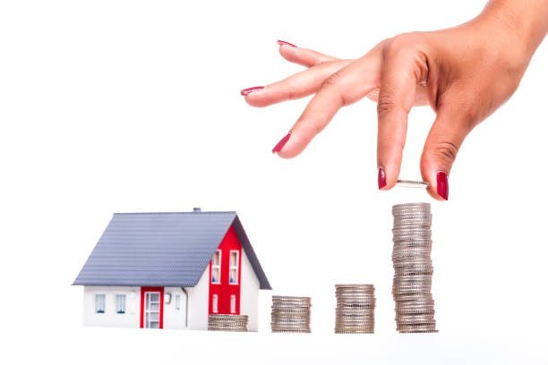 woman hand holding coin for saving on graphic with small house - oggetti personali foto e immagini stock