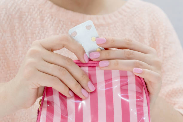 Woman hand holding contraceptive pill or birth control pill stock photo