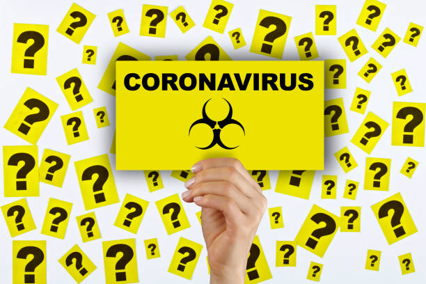 Woman hand holding corona virus sign. Question marks on the background. Woman hand holding corona virus sign. Lots of question marks on the white background. covid icon stock pictures, royalty-free photos & images