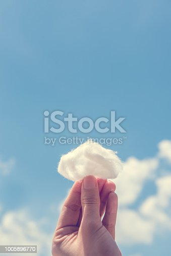 istock Woman hand holding cotton wool on cloud sky background. 1005896770