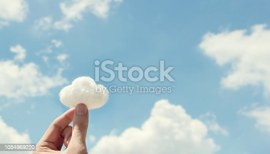 istock Woman hand holding cotton wool on cloud sky background. The development of the imagination. 1054969220