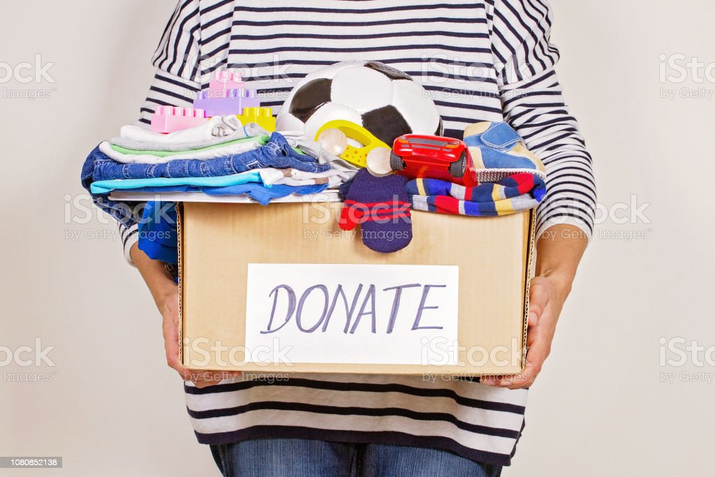 Mano de mujer caja de donación con ropa, juguetes y libros para la caridad foto de stock libre de derechos