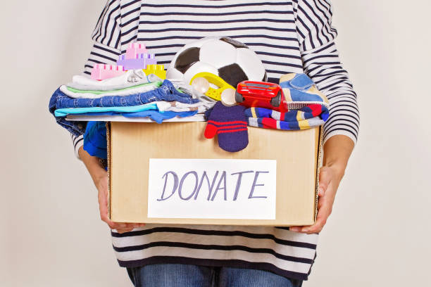 Woman hand holding donation box with clothes, toys and books for charity Woman hand holding donation box with clothes, toys and books. clothes in box stock pictures, royalty-free photos & images