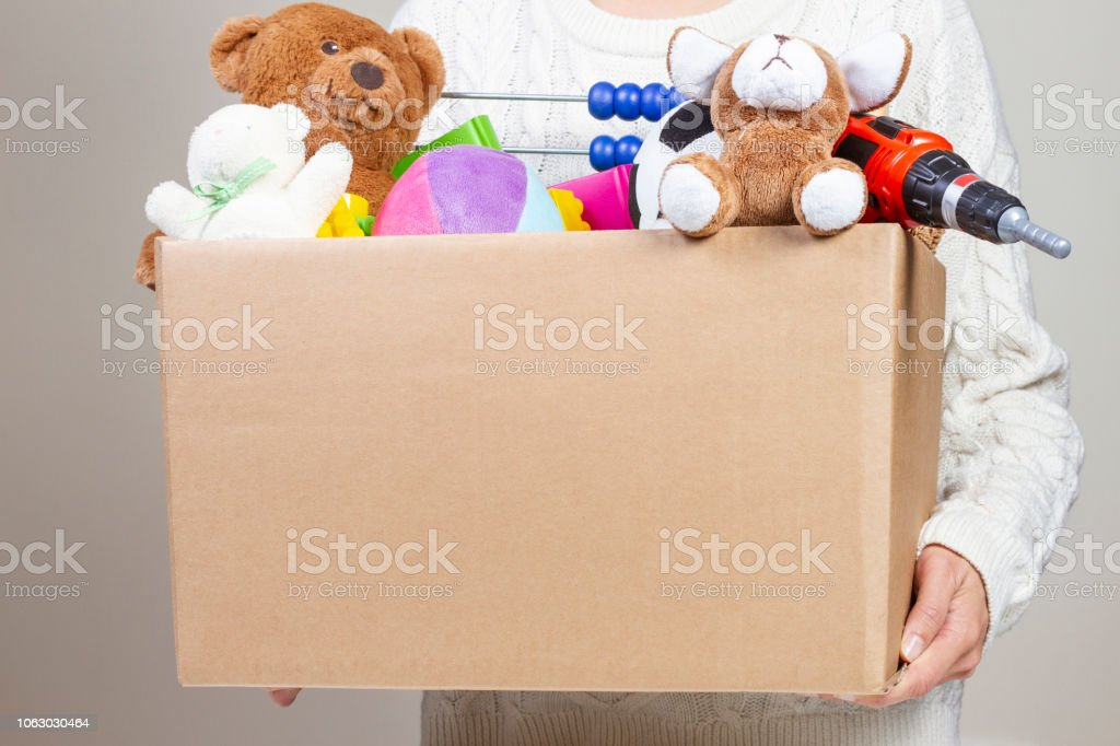 Woman hand holding donation box with clothes, toys and books.