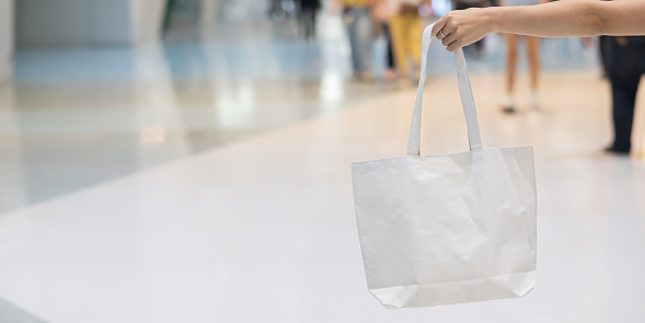 Woman hand holding Eco Shopping bag in store background with Copy space for text. Environmental Protection, Zero waste, Reusable, Say No Plastic, World Environment day and Earth day concept