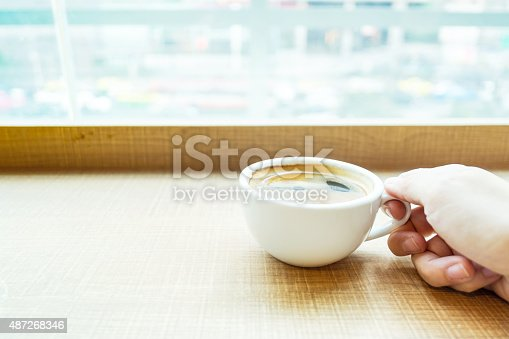 istock woman hand holding Espresso Coffee cup on wood table 487268346