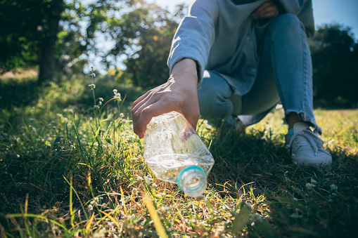 Woman hand holding garbage bottle plastic putting into recycle bag for cleaning