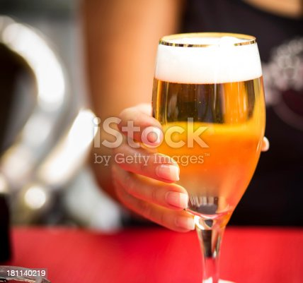 istock woman hand holding glass beer 181140219