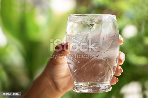 woman hand holding glass of cold and fresh water with ice, drinking outdoors