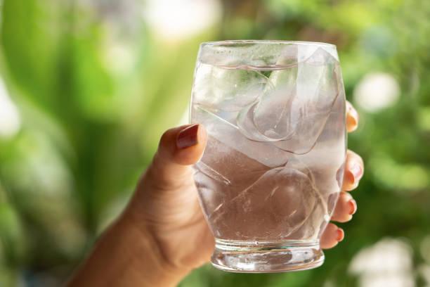 người phụ nữ tay cầm ly nước lạnh và nước ngọt với đá - cold water hình ảnh sẵn có, bức ảnh & hình ảnh trả phí bản quyền một lần