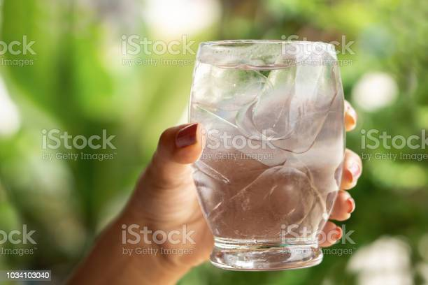 Photo of woman hand holding glass of cold and fresh water with ice