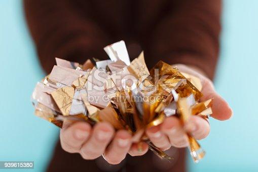 1016084100istockphoto woman hand holding golden confetti 939615380