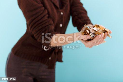 1016084100istockphoto woman hand holding golden confetti 939615452