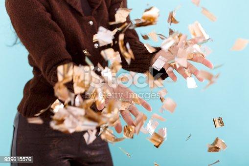 1016084100istockphoto woman hand holding golden confetti 939615576