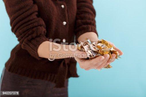 1016084100istockphoto woman hand holding golden confetti 940207078